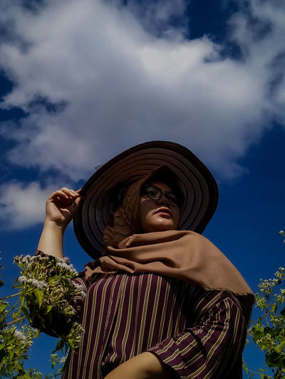 Low angle portrait of woman standing against sky