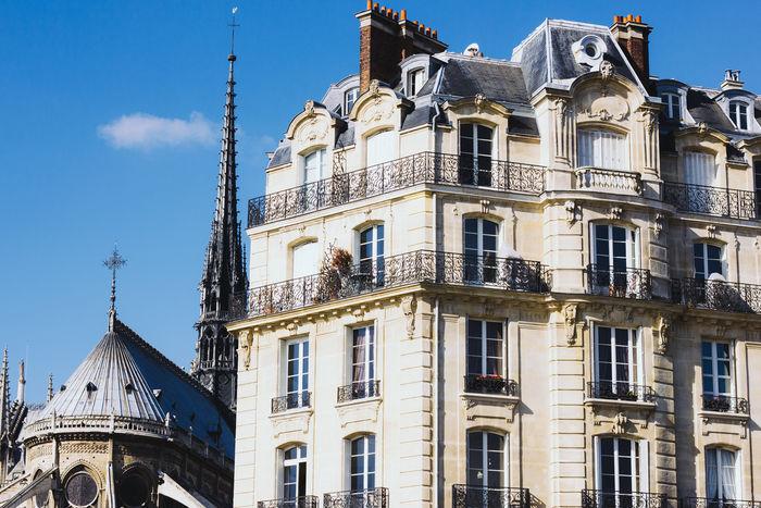 The Notre Dame de Paris and a Parisian building. Architecture Building Church City Façade Historic Notre Dame De Paris Outdoors Paris Tower