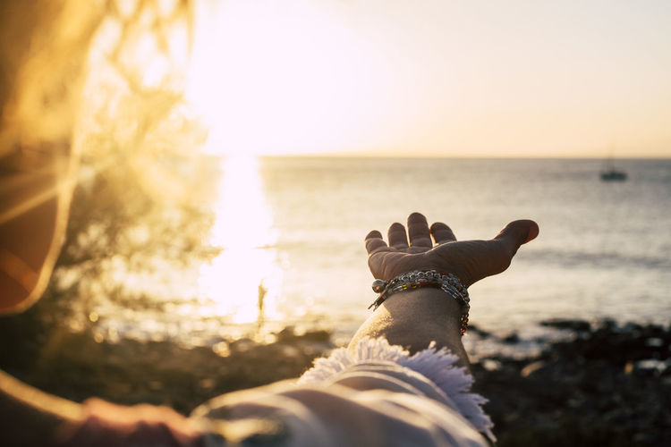 Cropped hand of woman gesturing at beach against sea and sky during sunset