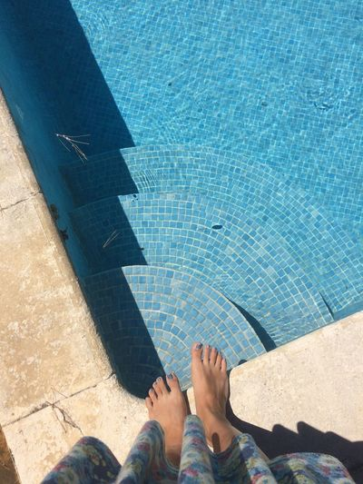 Low Section Of Woman Standing Against Swimming Pool