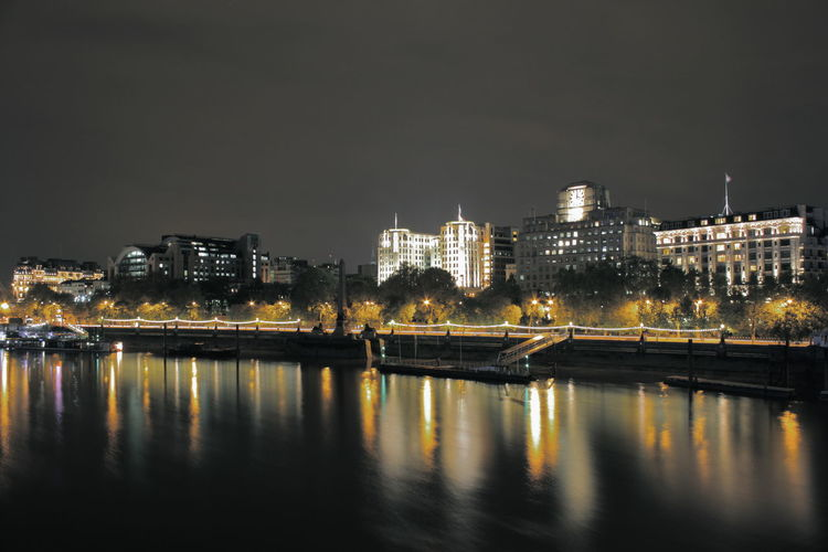 Thames river by illuminated buildings against sky