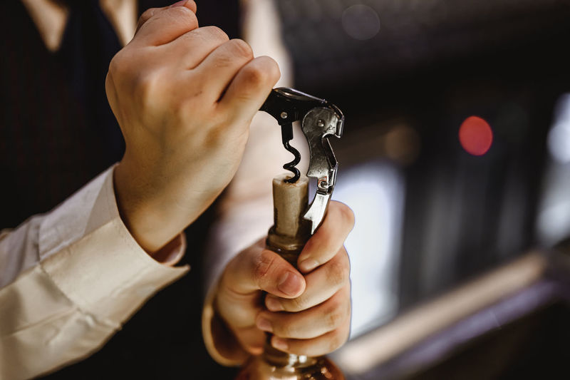 Midsection of man holding wine opener