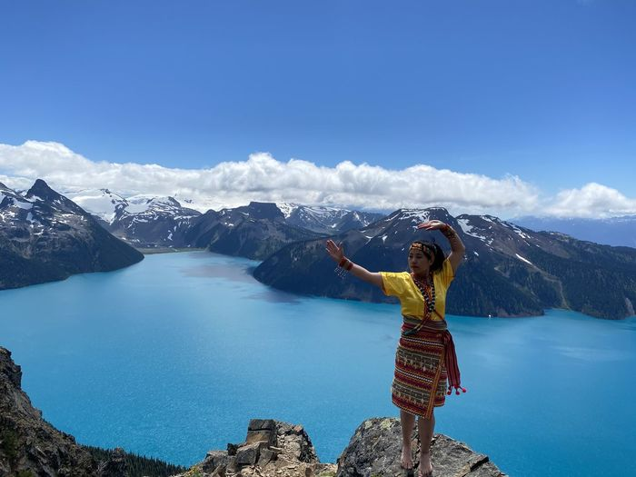 Full length of woman standing against lake and sky