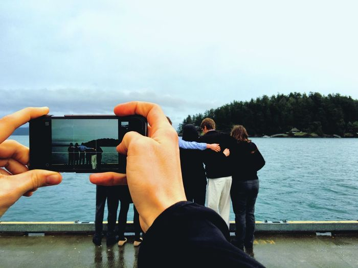 Cropped Image Of Hands Photographing Friends By Lake Against Sky
