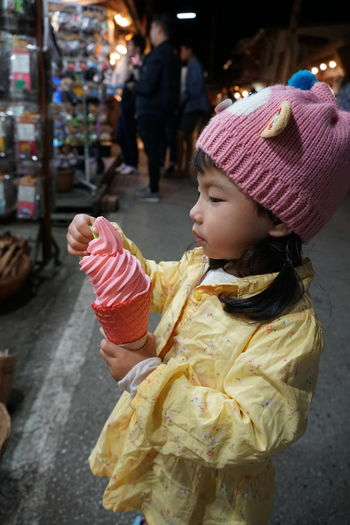 Side view of girl holding ice cream outdoors