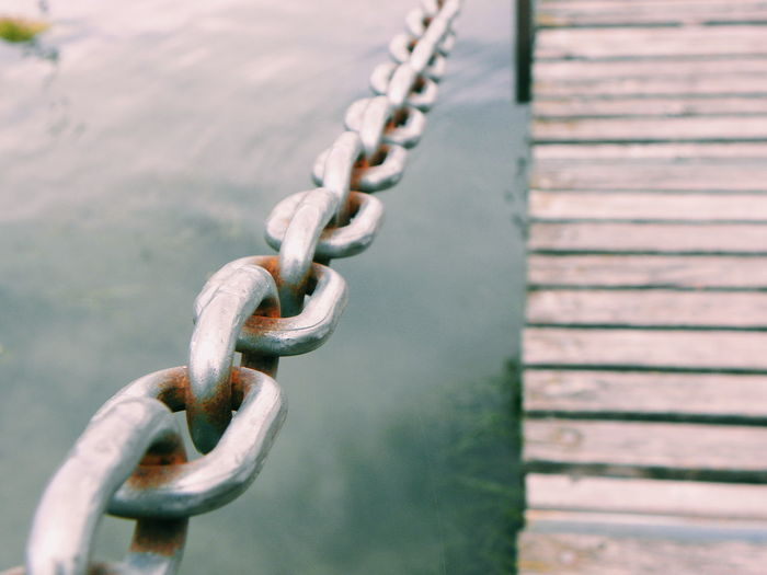 Close-up of rusty chain over lake