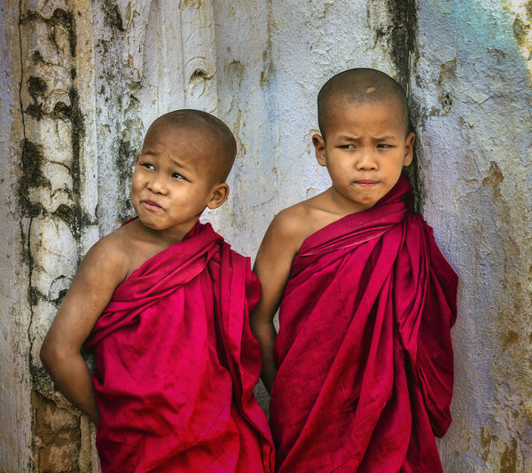Monks in traditional clothing standing against wall