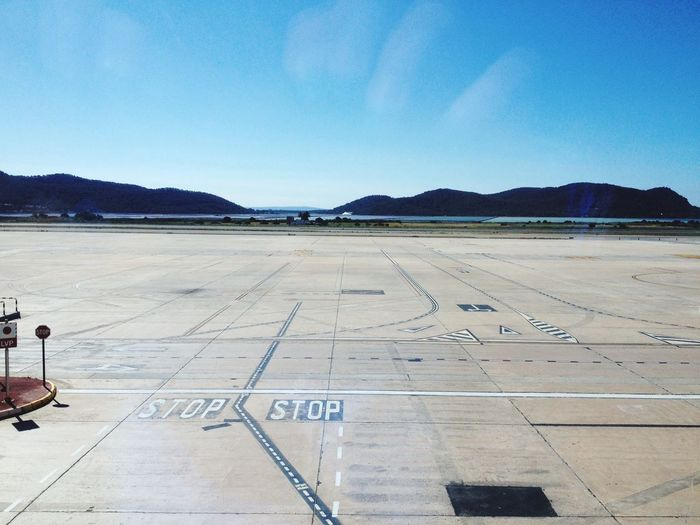 Empty airport runway against sky on sunny day