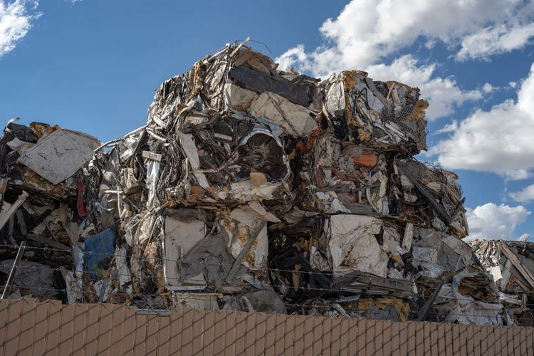 Low angle view of scarp garbage against sky