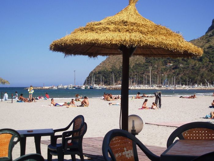 Thatched roof and chairs against people relaxing at beach
