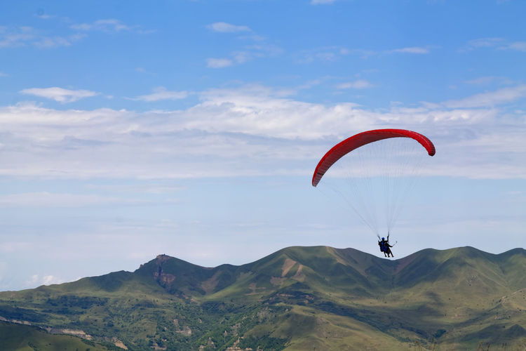 Person paragliding over mountains against sky