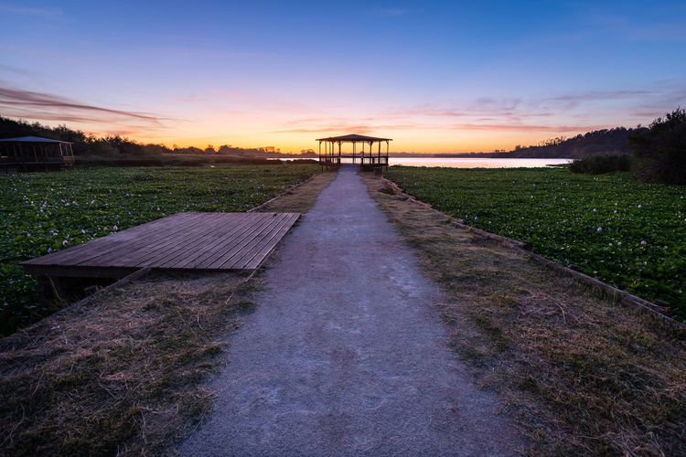Walkway amidst field against sky during sunset