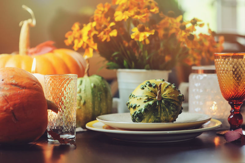 festive autumn table decoration for Thanksgiving with pumpkins and flowers Farm Table Setting Thanksgiving Country Life Decoration Festive Flower Food Food And Drink French Food Freshness Glass Harvest Healthy Eating Indoors  No People Orange Plate Ready-to-eat Serving Size Still Life Table Vegetable