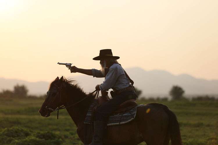 Horse Mammal Livestock Domestic Animals Domestic Hat Horseback Riding Animal Themes Ride Animal Riding Pets Vertebrate Sky Animal Wildlife One Animal Working Animal Real People Sunset Clothing Cowboy Cowboy Hat Herbivorous Ranch