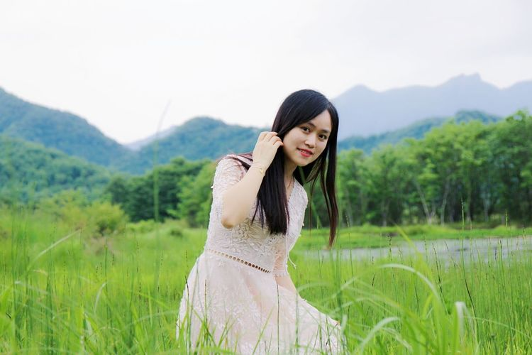 Portrait Of Smiling Beautiful Woman Kneeling Grassy Field Against Mountains