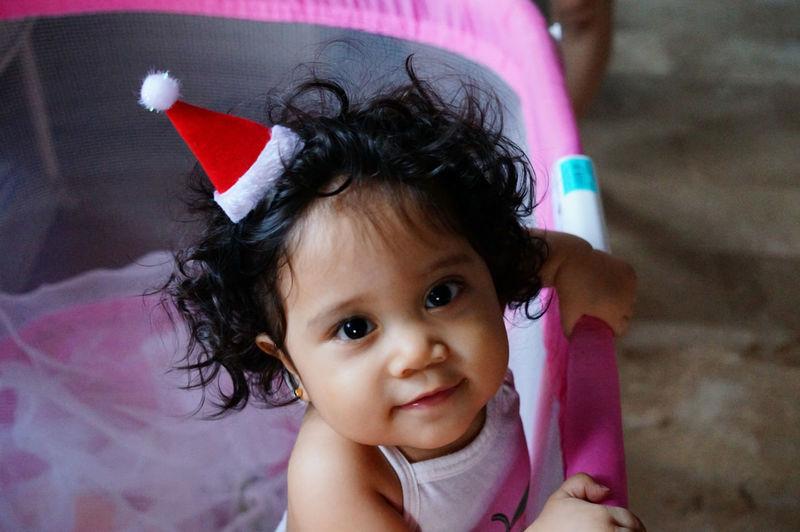 Baby Childhood Christmas Crib Cute Holiday Innocence Looking At Camera Santa Hat Smiling Curly Hair Playpen