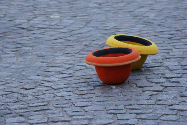 High angle view of red and yellow containers on cobbled street