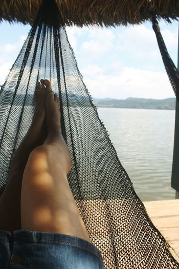 Low section of woman relaxing in hammock against lake