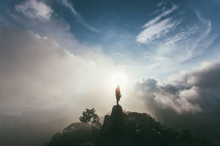 Silhouette Man Standing On Rock Against Clouds