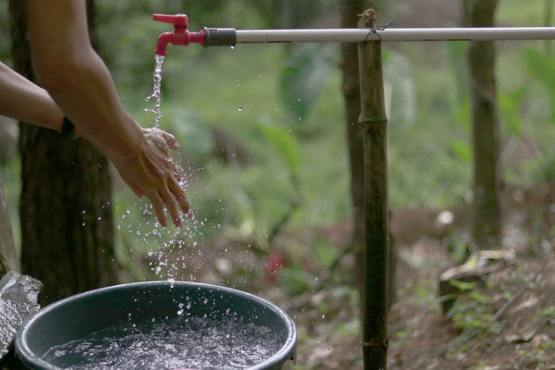Person washing hands from faucet outdoors