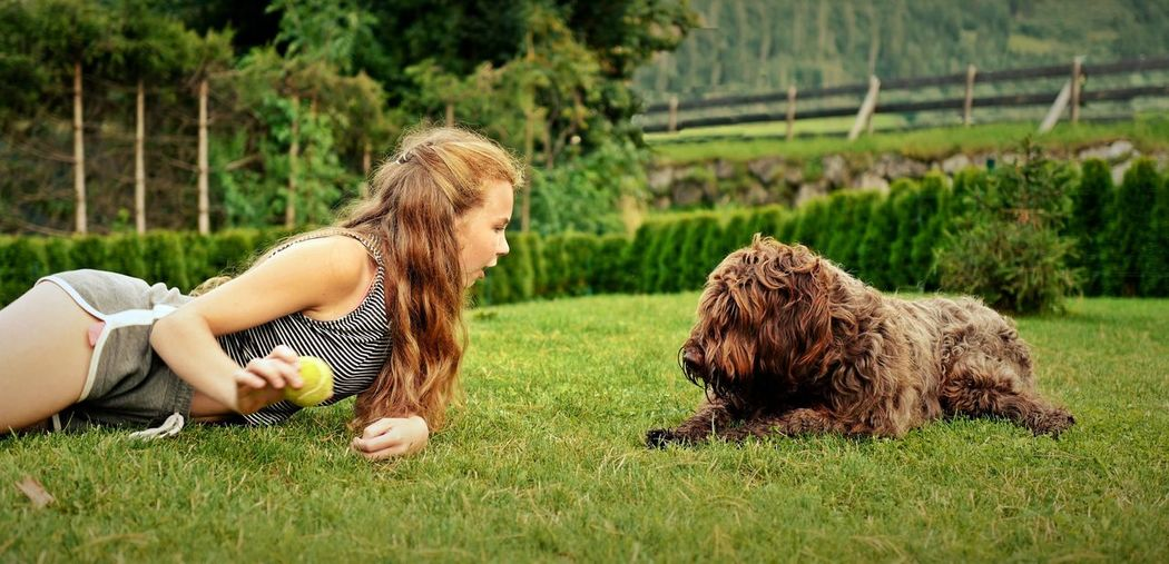 Side View Of Woman Lying On Grass While Playing With Pudelpointer