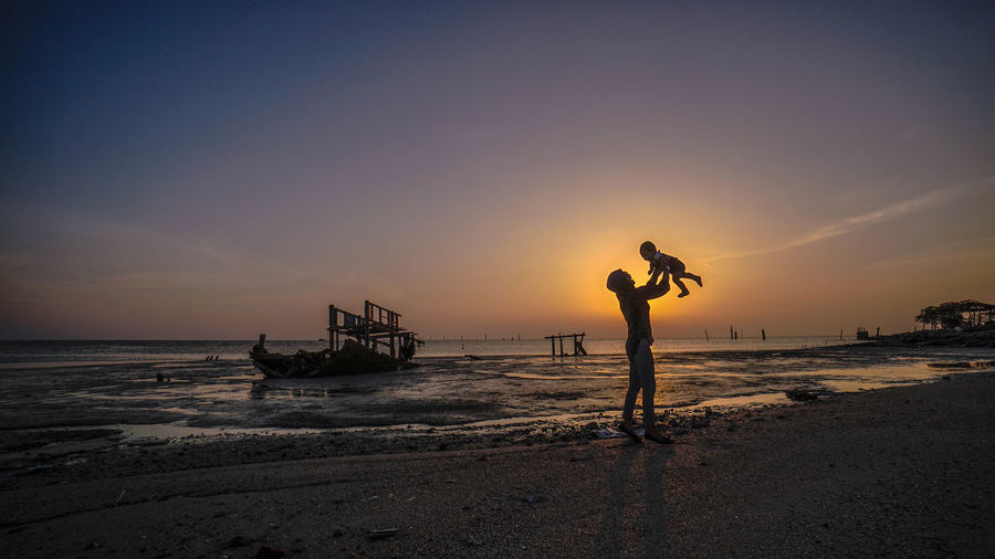 Woman holding baby while standing at beach against sky during sunset