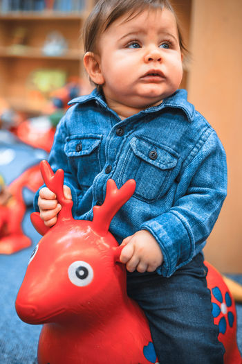 Babyboy Blonde Deer Childhood Close-up Cute Day Denim Home Interior Indoors  Inflatable  Lifestyles One Person Play Playground Playing Real People Red Color Ride A Horse Riding Toy