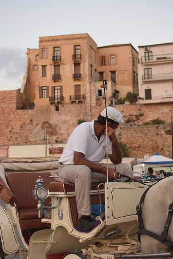 Care for a ride along the old port of Chania? One Person Real People Architecture Mode Of Transportation Building Exterior Built Structure Transportation Lifestyles Sitting Occupation Day City Leisure Activity Skill  Sky Coach Horse Vintage Retro Ride Summer Greek Islands Crete Traditional