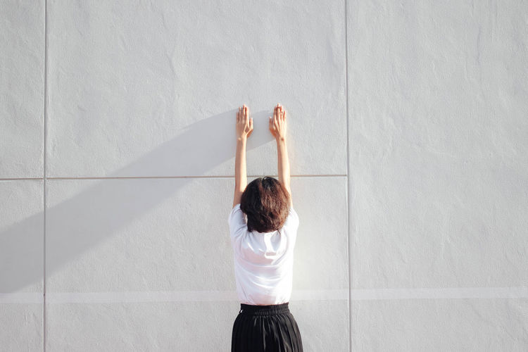 young woman wearing black shirt arm raised trying to climb the wall Architecture Arms Raised Day Give Up Indoors  Leisure Activity Lifestyles One Person People Real People Rear View Standing Wall - Building Feature White Color Women Young Adult Young Women