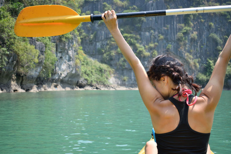 Rear view of woman holding oar while sitting on kayak in sea