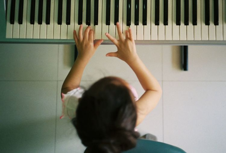 Directly above shot of girl playing piano at home