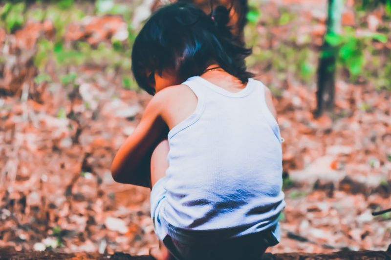 Rear view of girl crouching on land