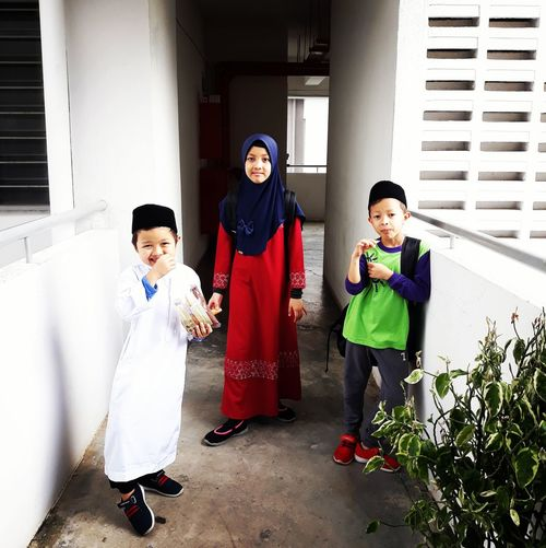 Portrait of siblings standing in corridor of building
