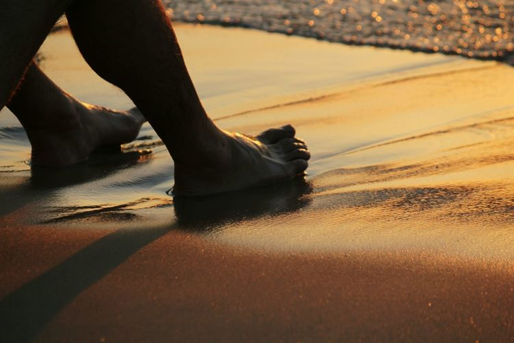 Low section of person relaxing on sandy beach at sunset