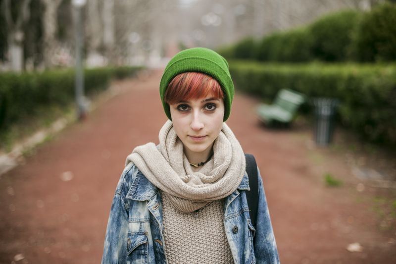 Portrait of young woman standing at park