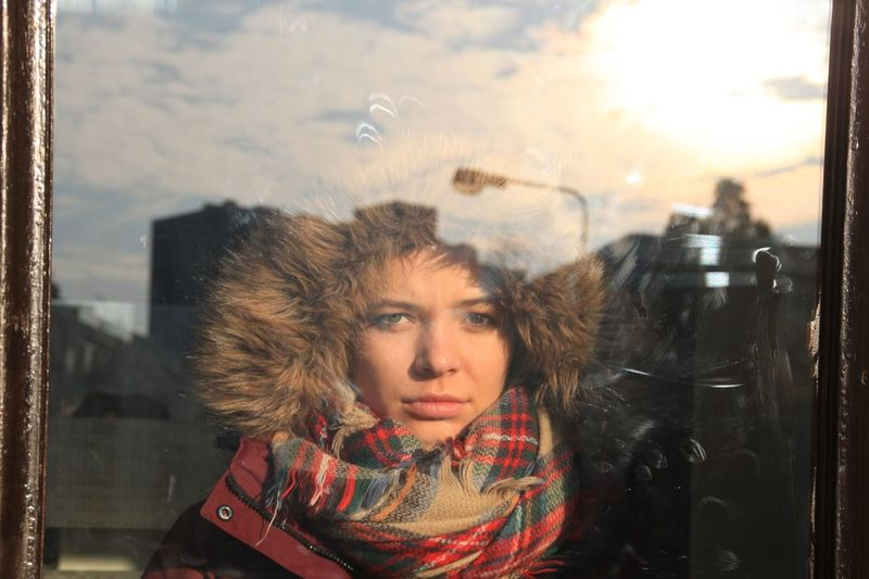 Portrait Of Young Woman Wearing Warm Clothing Seen Through Window