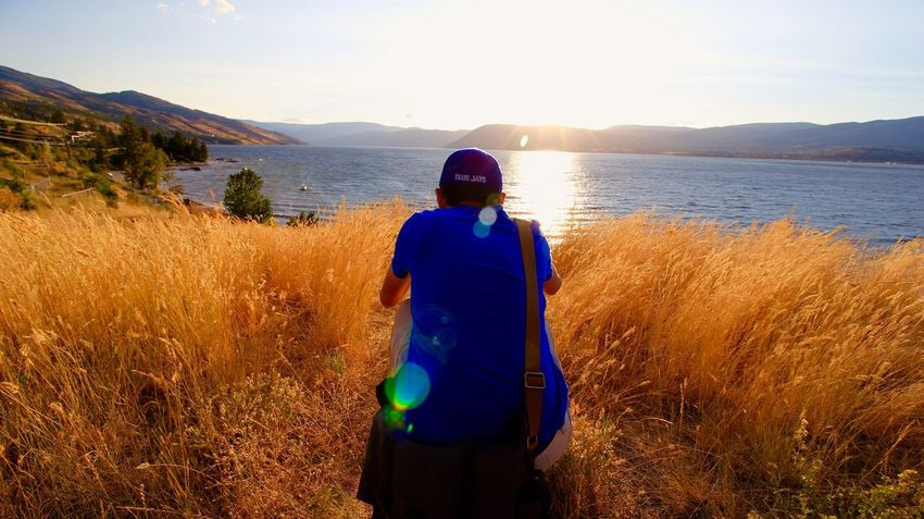 Rear View One Person Standing Three Quarter Length Nature Real People Mid Adult Sunlight Tranquility Landscape Sunset Grass Scenics Leisure Activity Only Women Lifestyles Outdoors Growth Beauty In Nature Adventure Beautifulbc Kelowna Sunlight Wheat Rural Scene