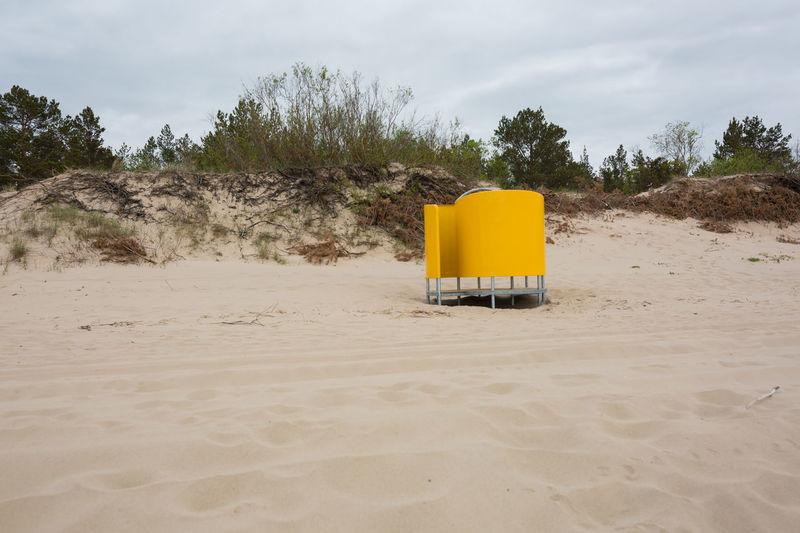 Lifeguard hut on desert land against sky
