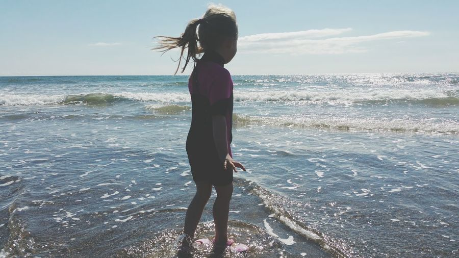 Rear view of girl standing at beach against sea