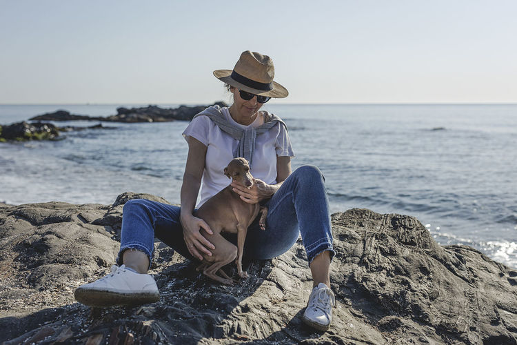 Sitting Sea Water Rock - Object Rock Full Length Leisure Activity Real People Casual Clothing Solid Lifestyles Hat Land One Person Beach Young Adult Beauty In Nature Young Men Nature Horizon Over Water Fashion Outdoors