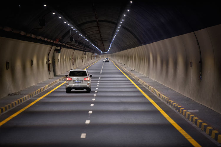 Cars moving in illuminated tunnel