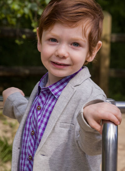 Portrait of cute boy standing on merry-go-round at playground