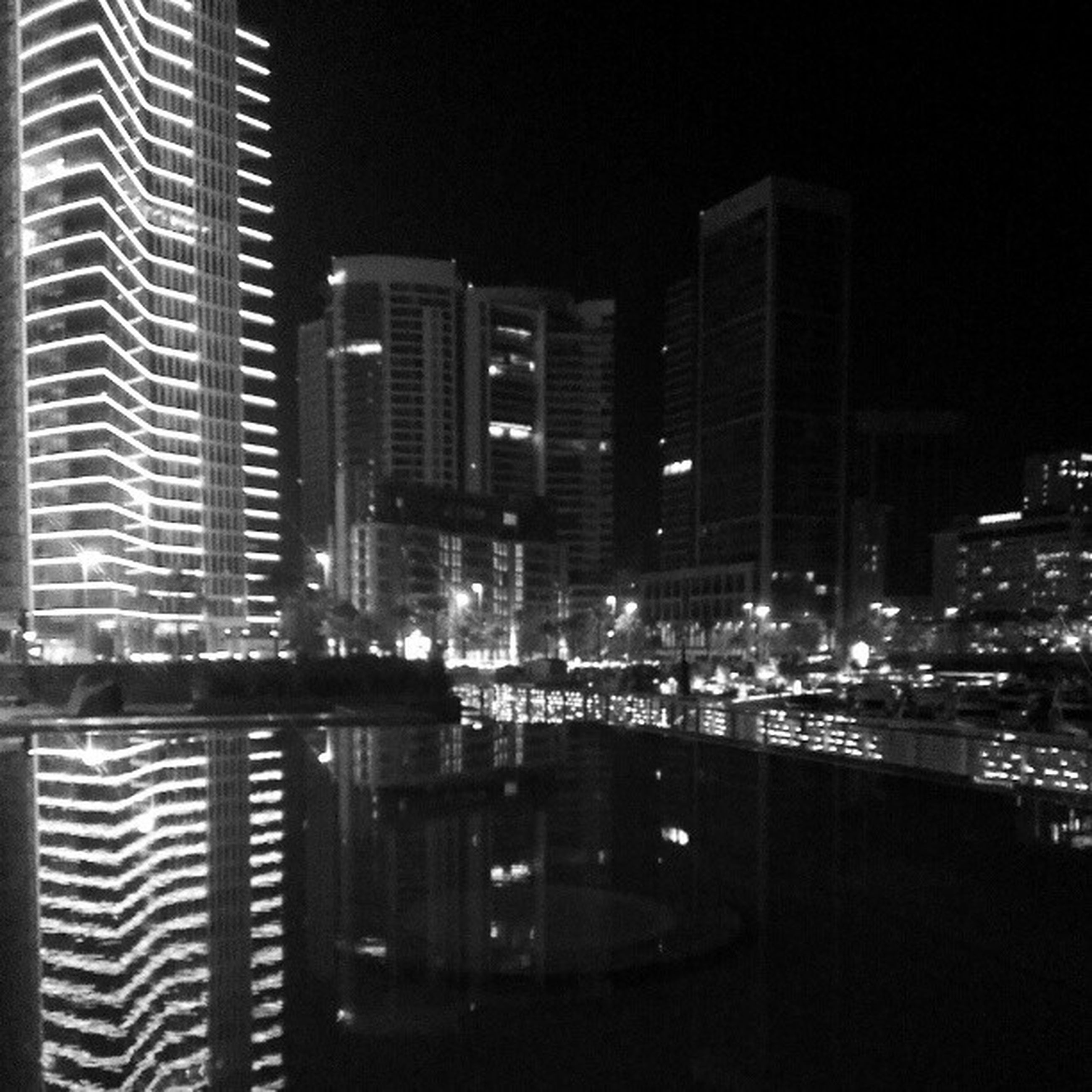 building exterior, city, architecture, skyscraper, illuminated, night, built structure, modern, office building, cityscape, tall - high, tower, urban skyline, financial district, building, city life, glass - material, reflection, residential building, development