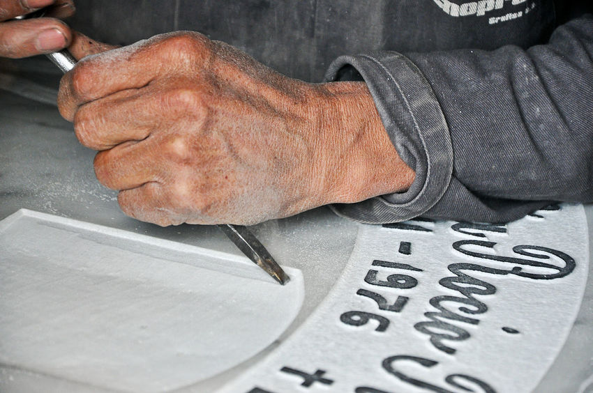 A tombstone engraver working on a tombstone. Adult Close-up Colombia Cundinamarca Day Death Dust Engrave Gray Hands Human Hand Indoors  Labor Men One Person Only Men People Tombstone Work Worker Working