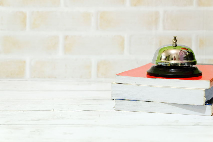 Ring bell and a stack of books. Copy space for text or logo. Desk Table Office Ring Bell Bell Ring Ting Alarm Copy Space Object Backgrounds Stack Books Library Front Desk Front Counter Lobby Hotel Motel