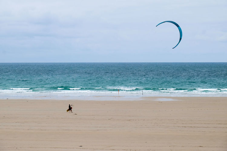 Man Kiteboarding At Beach Against Sky