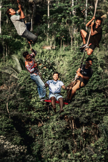 Men in traditional clothing hanging on tree in forest