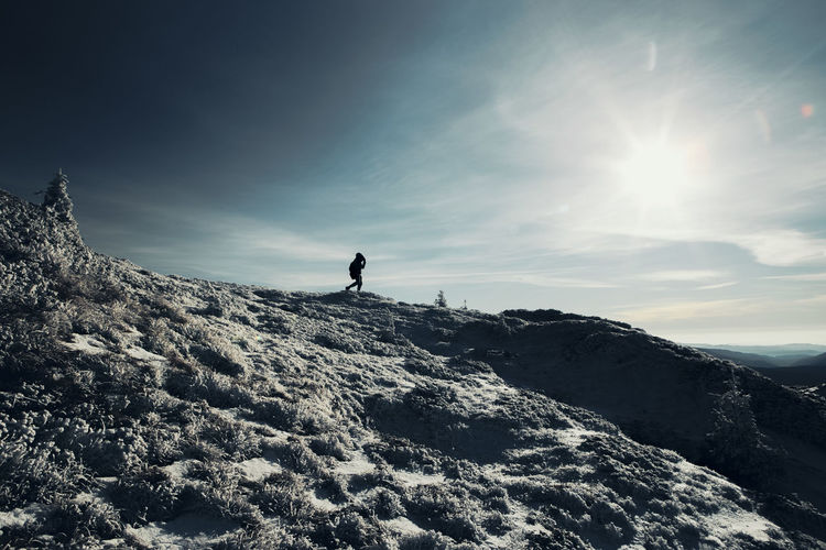 Low angle view of man standing on mountain against sky