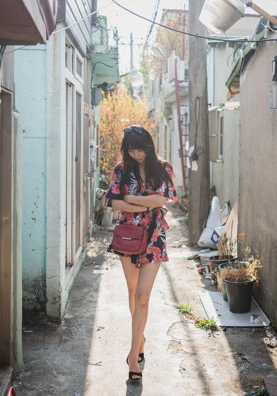 Woman walking in alley amidst buildings