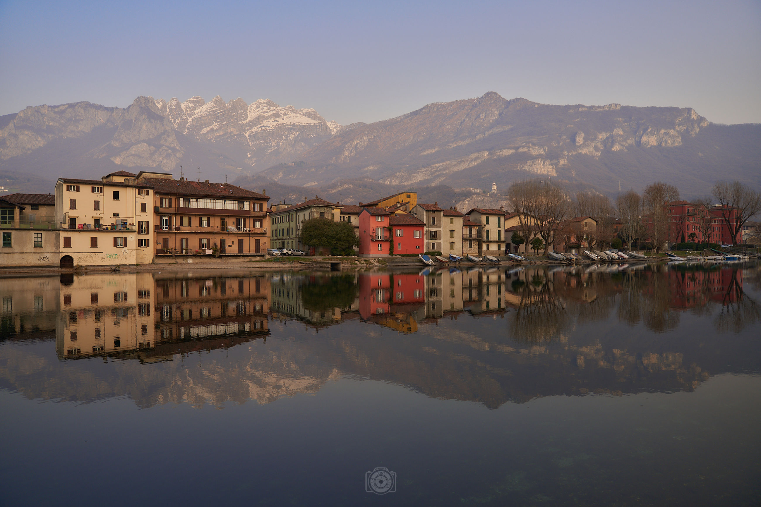 reflection, water, mountain, architecture, morning, sky, building exterior, built structure, building, nature, lake, mountain range, dusk, city, house, scenics - nature, travel destinations, no people, beauty in nature, landscape, cityscape, environment, residential district, travel, outdoors, tranquility, town, waterfront, clear sky, tourism, land